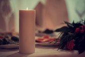 Candle and flowers on a festive table — Стоковое фото