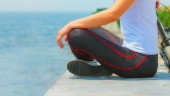 Girl sitting at seaside and relaxing, woman fitness — Stock Photo