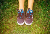 Girl running shoes closeup, green grass, woman fitness — Stockfoto