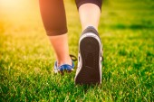 Girl running shoes closeup, green grass, woman fitness — Fotografia Stock