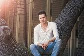 Stylish casual serious man sitting on tree. — Stock Photo