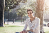 Handsome casual happy man sitting in park. — Stock Photo