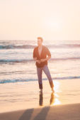Handsome sexy and serious man standing at beach. — Stock Photo