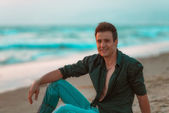 Casual sexy and smiling man relaxing at beach. — Stock Photo