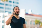 Handsome happy and casual young man with cellphone talking — Stock Photo
