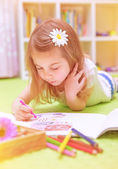 Preschooler girl painting with colorful pencil — Stock Photo