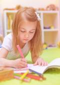 Preschooler girl painting in daycare — Stock Photo