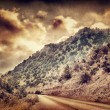 Grunge photo of road in the mountains — Stock Photo #54163665