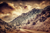 Grunge photo of road in the mountains — Stock Photo