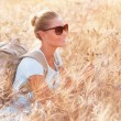 Happy traveler in wheat field — Stockfoto