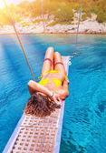 Sexy woman tanning on sailboat — Stock Photo