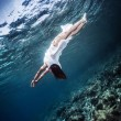 Active woman diving to the sea bottom — Stock Photo #57552453