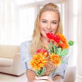 Happy woman with flowers at home — Stockfoto