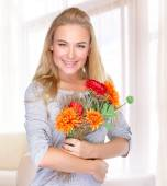 Happy woman with autumn flowers — Stock Photo
