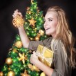 Happy girl decorating Christmas tree — Stock Photo #60481367
