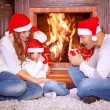 Happy family by fireplace — Stock Photo #60693075