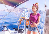 Beautiful woman behind helm of sailboat — Stock Photo