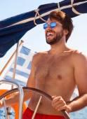 Happy guy behind wheel of sailboat — Stock Photo