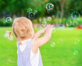 Baby girl play with soap bubbles — Stock Photo
