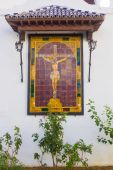 Small altar with a Christ Andalusian tiles on a white wall — Stock Photo