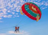 Couple parasailing on the beach — Stock Photo