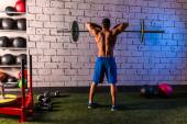 Barbell weight lifting man rear view workout gym — Stockfoto