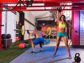 Barbell weight lifting man woman rising kettlebell — Stock Photo