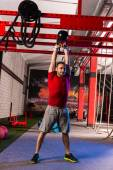 Kettlebell swinging man weightlifting workout gym — Stock Photo