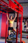 Toes to bar woman pull-ups 2 bars — Stock Photo