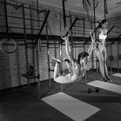 Gym girls muscle ups rings swinging workout — Stock Photo