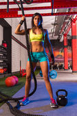 Beautiful fitted girl at gym with black rope — Stock Photo