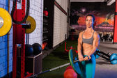 Gym girl lifting a barbell with fit body — Stock Photo
