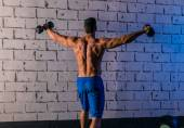 Gym man rising hex dumbbells weightlifting rear — Stock Photo