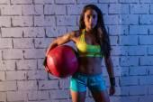 Brunette gym girl holding weighted ball — Stockfoto