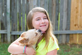Blond kid girl with chihuahua pet dog playing — Stock Photo