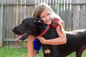Great dane and kid girl hug playing outdoor — Zdjęcie stockowe