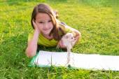 Kid girl and puppy dog at homework lying in lawn — Stock Photo