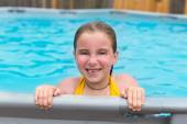 Blond girl swimming in the pool with red cheeks — Stock Photo