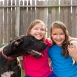 Twin sisters puppy pet dog and great dane playing — Stock Photo #57790131
