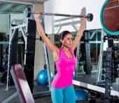 Brunette girl wide grip barbell shoulder press gym — Stock Photo