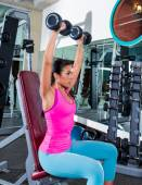 Girl at gym seated dumbbell shoulder press — Stock Photo