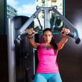 Brunette woman seated chest press machine gym — Stock Photo