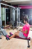 Seated cable row man rows at gym pulley machine — Stockfoto