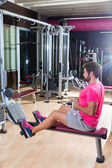 Seated cable row man rows at gym pulley machine — Fotografia Stock