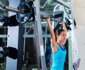 Brunette girl in multipower barbell at gym smith — Stock Photo