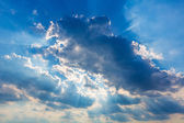 Dramatic cloudy sky clouds with real sun beams — Stock Photo