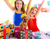Girl friends party dancing with presents and puppy — Stock Photo