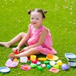 Toddler kid girl playing with food toys sitting in turf — Stock Photo #63241519