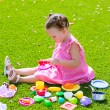 Toddler kid girl playing with food toys sitting in turf — Stock Photo #63241571
