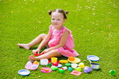 Toddler kid girl playing with food toys sitting in turf — Stock Photo
